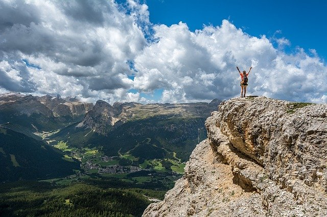 Man on a mountain with hands in the air. Success.
